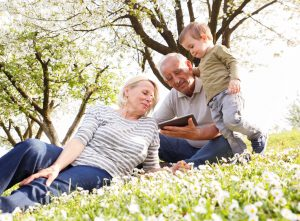 Grandparents with grandson enjoying the sunny spring day outdoors. They are looking something on tablet.